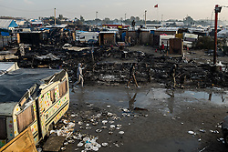 October 26, 2016 - Calais, France - Migrants walk in the Calais Jungle between burned down huts in Calais, France on 26 October 2016.. Huge fires destroyed a mayor part of the refugee camp today. (Credit Image: © Markus Heine/NurPhoto via ZUMA Press)