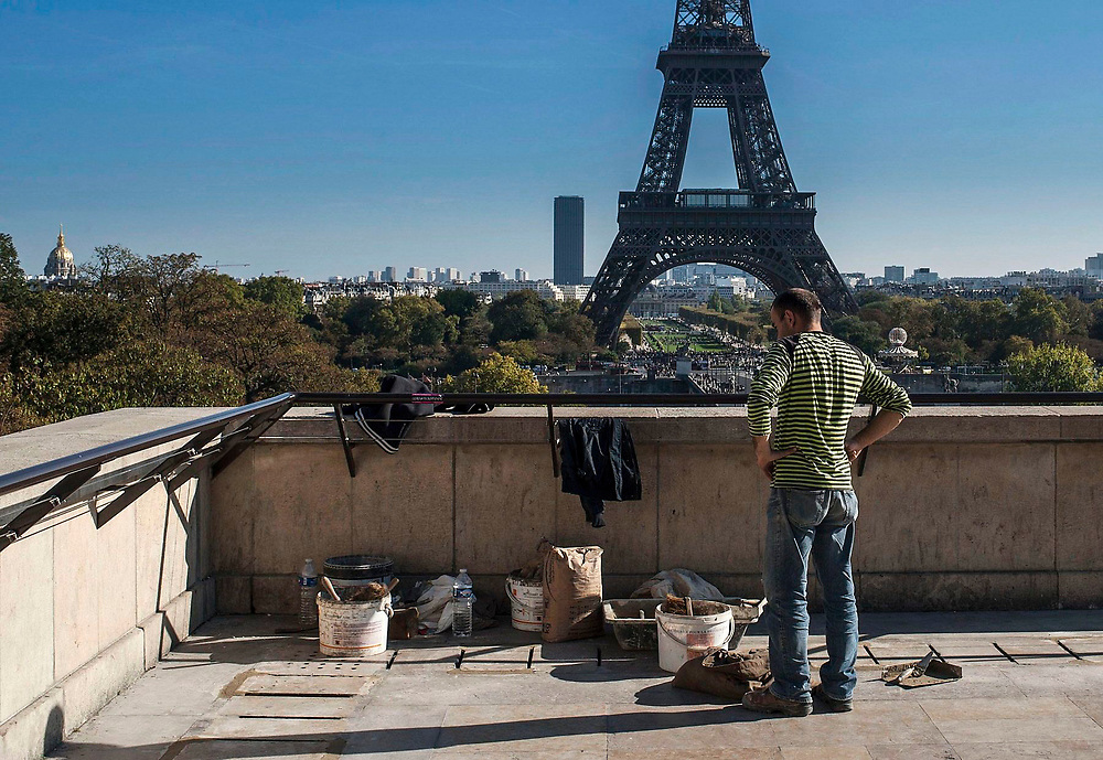 A construction worker in front of the  Eifel Tower, Paris