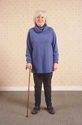 Portrait of woman with disability using walking stick,
