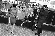A model gets photographed by a photographer, whilst a homeless man sits and watches, in a street in the Shibuya district of the city, Tokyo, Japan.