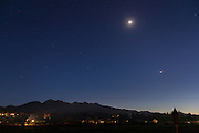 Venus and Mars, very close together, share the sky with the crescent moon above the Olympic Range.