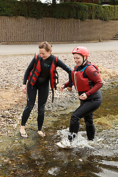 Instructor helping visually impaired girl following rafting activity at the National Water Sports Centre.