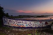 The Folly Boat a landmark public art project along the marsh at sunset in Folly Beach, SC.
