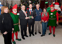 "City Manager Eileen Cabanel, ""Tinsel"", Christmas Village's Mayor Patrick Wood, Laconia's Mayor Michael Seymour, Councilors Bob Hamel and Ava Doyle and ""Twinkle"" pass  the key to Christmas Village to Mayor Seymour as they celebrate opening night Thursday evening.   (Karen Bobotas/for the Laconia Daily Sun)"