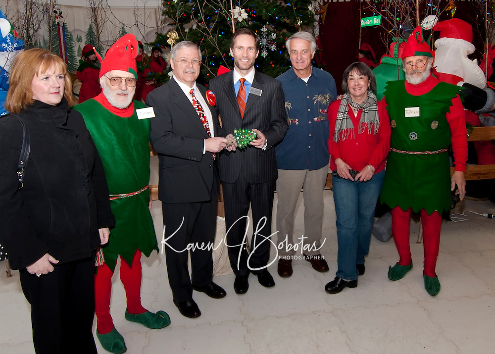 """City Manager Eileen Cabanel, """"Tinsel"""", Christmas Village's Mayor Patrick Wood, Laconia's Mayor Michael Seymour, Councilors Bob Hamel and Ava Doyle and """"Twinkle"""" pass  the key to Christmas Village to Mayor Seymour as they celebrate opening night Thursday evening.   (Karen Bobotas/for the Laconia Daily Sun)"""