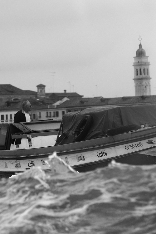 Black and white photo of man on Boat in Venice, Italy