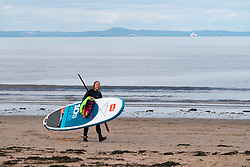 Portobello, Scotland, UK. 11 May 2020. Late afternoon views of popular Portobello beach and promenade. Despite occasional police patrols, the public were determined to relax and enjoy sitting in the sunshine. Woman carries her stand up paddle board along the beach. Iain Masterton/Alamy Live News