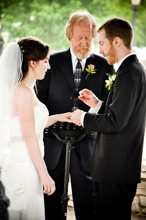 Caitlin & Alex exchange rings under the gazebo at Walton Island, Elgin, IL. Alex's father officiated over the ceremony