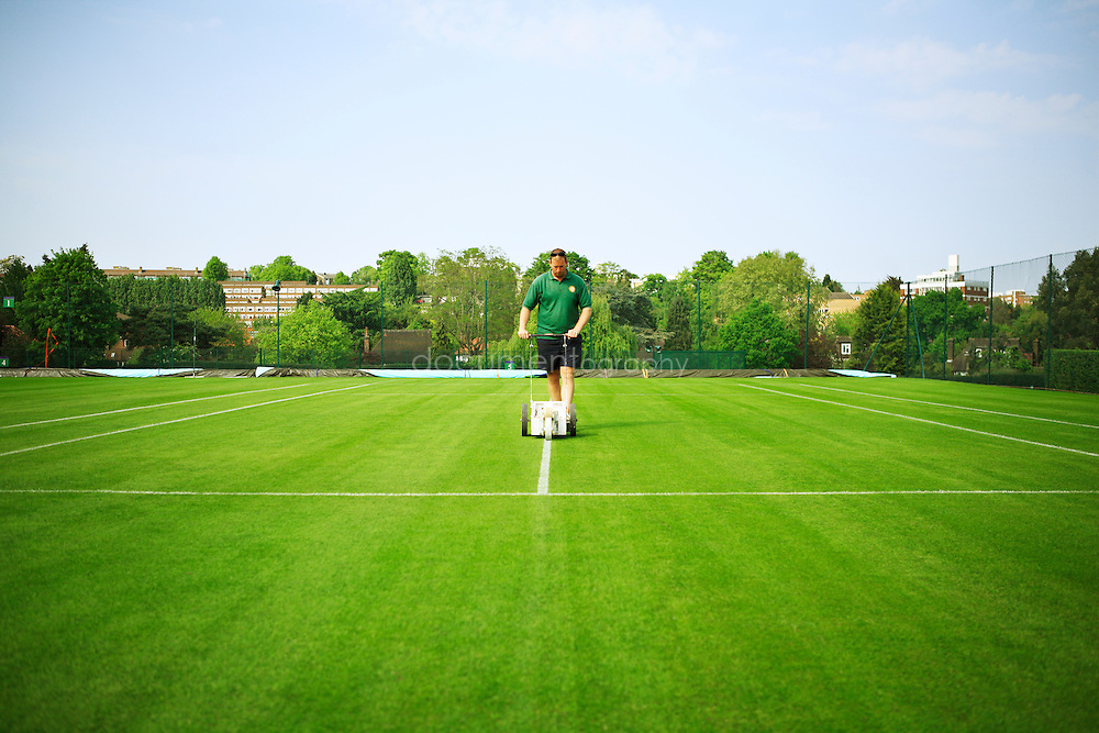 A gardener draws the lines on one of Wimbledon's tennis court