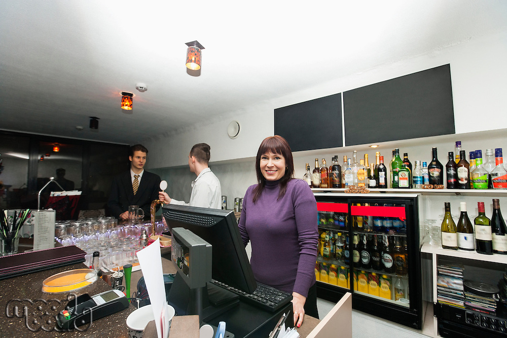 Portrait of female cashier with manager and bartender at bar counter