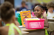 Torian Julius, 7, 1st grade, of Cedar Rapids smiles at a classmate as she reads a book on the first day of school at Polk Elementary School, 1500 B Avenue NE, in Cedar Rapids on Thursday morning, July 21, 2011.