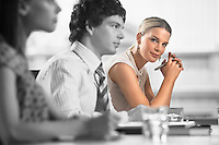 Portrait of young businesswoman with colleagues in a meeting