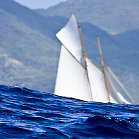 The masts of the Schooner Eleanora rise above the waves off the coats of Antigua during Antigua Classic Yacht Regatta This race is  one of the worlds most prestigious traditional yacht races. It is held annually
