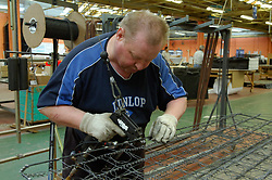 Remploy factory; Forest Hall; Newcastle; UK 2007, Remploy provides specialist employment services to disabled people and those who face barriers to employment, Man making mattress fastening wiring