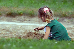 01 October 2016:  a young girl dressed in IWU cheerleaders uniforms play just outside the stadium in the sand box at the end of the long jump during an NCAA division 3 football game between the Wheaton Thunder and the Illinois Wesleyan Titans in Tucci Stadium on Wilder Field, Bloomington IL (Photo by Alan Look)