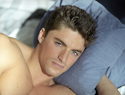 close up of a handsome man in bed