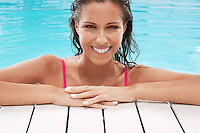 Woman in Swimming Pool resting on poolside portrait