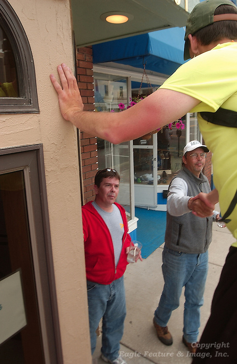 25 year old Neil Sauter (right) gets a handshake of support from Dave Boal (center) as fellow Charlevoix, Michigan resident Chris Jones (left)  looks on.  Suater is walking from Toledo, Ohio to Ironwood, Michigan on stilts to raise money and awarness for Cerebral Palsy.