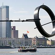 Nederland Rotterdam 9 juli 2010 20100709 Stadsgezicht Kop van Zuid / Noordereiland, rivier de Maas.      Op de voorgrond zitten meeuwen in een stalen kunstwerk, een lijn met daaraan een circelvormig object en vaart een motorboot over de rivier de Maas. Op de achtergrond  appartementen op het Noordereiland en o.a. hoogbouw nieuwbouw het hoogste kantoorgebouw van Nederland De Maastoren op de Kop van Zuid. , stadachtig, stadgezicht, stads, stadsaanzicht, stadsbeeld, stadscentrum, stadsdeel, stadse, stadsgezicht, stadshaven, stadshavens, stadslandschap, stadsontwikkeling, stadsuitbreiding, stadsuitbreidingslocaties, stadsvernieuwing, stalen, stedebouw, stedelijk gebied, stedelijk lokatie, stedelijke, stedelijke planning, stedelijke vernieuwing, steden, stedenbouw, steeds, steedse, stilleven, straatbeeld, straatgezicht, street scenery, streetscene, sunshine, the netherlands, the sky is the limit, toren, torens, tower, uitbreidingsgebieden, urban landscape, urbanisatie, urbanisering, urbanisme, urbanistisch, urbanistische, vaart, varen, vastgoed, vernieuwing, vernieuwing stedelijk, vervoer over water, vessel, vogel, vogels, vrij, water, water level, Water Management Authority, waterbeheer, Waterbeheerplan, watergang, waterhuishouding, waterlevel, watermanagement, watermassa, waterniveau, Waterpeil, waterplan, wolkenkrabber, wolkenkrabbers, wonen aan het water, woningaanbod, woningblok, woningblokken, woningen, woonblok, woonblokken, zonnig weer , sculpture, sculpturen, sculptuur, skyline, Skyscraper, skyscrapers, staal, staaldraad, staaldraden, stadFoto: David Rozing