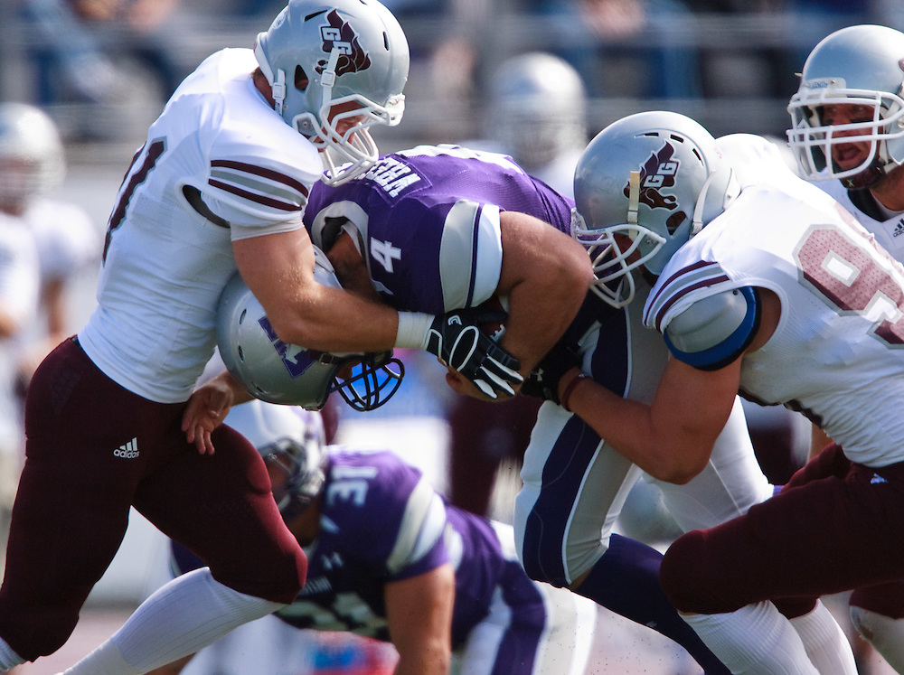 London, ONT.; September 17, 2011 -- Ottawa's  Ugo Levesque, left, and Alex Adams team up to take down Western's Rahul Madan during the Gee Gee's 41- 13 loss to the Mustangs at TD Waterhouse Stadium in London, Ontario, September 17, 2011.  <br /> <br /> (GEOFF ROBINS/ Ottawa Citizen)