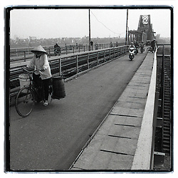 View of the Long Bien bridge. A vietnamese woman rides a bicycle wearing the classic conic hat. She carries two big buckets. Some motorbikes are about to pass her.