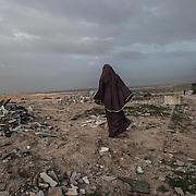"""Bet Hanon, quartiere a nord della striscia di Gaza quasi al confine con Erez. Una delle zone piu colpite dall'attacco israeliano """"Margine protettivo"""". Gli enormi palazzi sono completamente distrutti e sventrati. La popolazione, a distanza di sei mesi dalla fine della guerra, vive tra le macerie della propria casa, al freddo, senza luce, gas e acqua. Nella foto una donna cammina tra le macerie accatastate a terra."""