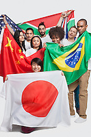 Group of multi-ethnic friends holding various national flags against white background