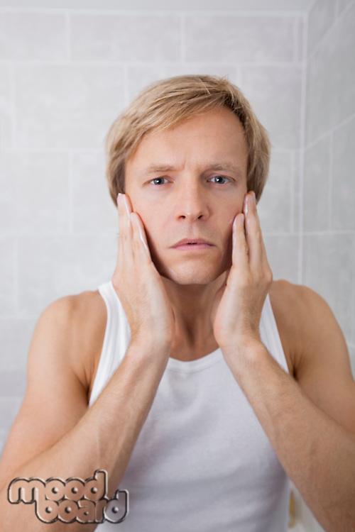 Portrait of man applying aftershave moisturizer in bathroom