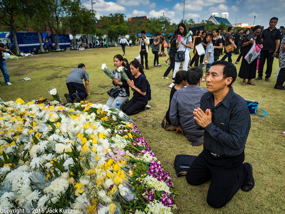 20 OCTOBER 2016 - BANGKOK, THAILAND: People mourning the death of Bhumibol Adulyadej, the King of Thailand, pray for His Majesty at Sanam Luang. Sanam Luang, the Royal Ceremonial Ground, is packed with people mourning the Monarch's death. The King died Oct. 13, 2016. He was 88. His death came after a period of failing health. Bhumibol Adulyadej was born in Cambridge, MA, on 5 December 1927. He was the ninth monarch of Thailand from the Chakri Dynasty and is also known as Rama IX. He became King on June 9, 1946 and served as King of Thailand for 70 years, 126 days. He was, at the time of his death, the world's longest-serving head of state and the longest-reigning monarch in Thai history.       PHOTO BY JACK KURTZ