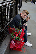 A young man with a bouquet of red roses awaits his girlfriend, on 15th February 2017, in Piccadilly Circus, London borough of Westminster, United Kingdom.