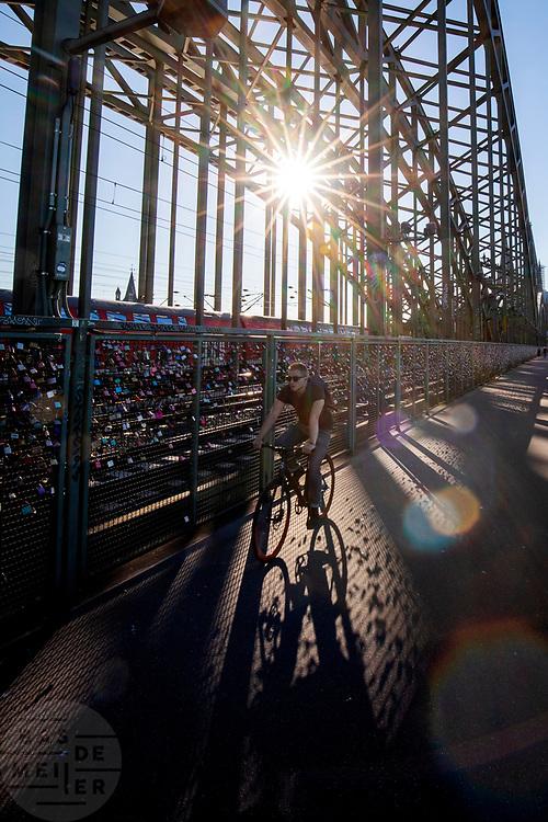 In Keulen rijdt een fietser over de brug met de liefdessloten. Koppels hangen sloten aan de brug om te laten weten dat ze van elkaar houden.<br /> <br /> In Cologne a man passes the locks of love hanging on the bridge.