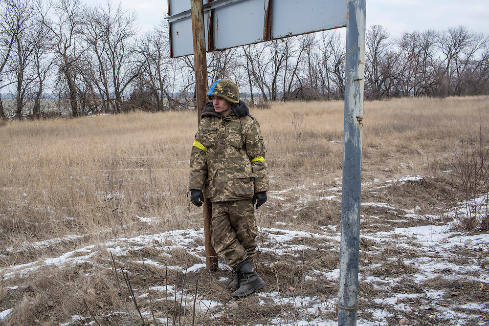 ARTEMIVSK, UKRAINE - FEBRUARY 19: A Ukrainian soldier from a unit based in Zaporizhia relaxes by the roadside after leaving Debaltseve on February 19, 2015 in Artemivsk, Ukraine. Ukrainian forces started withdrawing from the strategic and hard-fought town of Debaltseve yesterday being effectively surrounded by pro-Russian rebels. (Photo by Brendan Hoffman/Getty Images) *** Local Caption ***