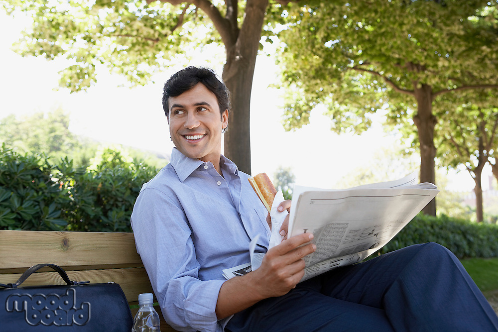 Businessman with sandwich and newspaper sitting on park bench