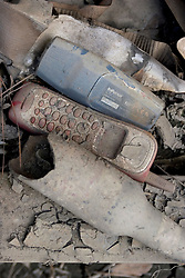 01 October, 05.  New Orleans, Louisiana. Lower 9th ward. Hurricane Katrina aftermath. <br /> The remnants of the lives of ordinary folks, now covered in mud as the flood waters recede.  A phone, television remote control and broken bottle lie in the dirt.<br /> Photo; ©Charlie Varley/varleypix.com