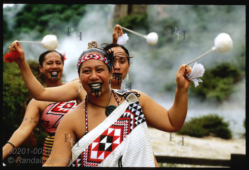 Tattooed Maori women perform traditional dance with small pompons at Waimangu Volcanic Valley; Rotorua, New Zealand.