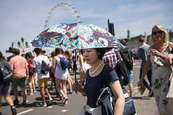 © Licensed to London News Pictures. 07/07/2017. London, UK. A visitor shades herself from the sun as she crosses Westminster Bridge as parts of the United Kingdom enjoy high temperatures and blue sky. Photo credit: Peter Macdiarmid/LNP