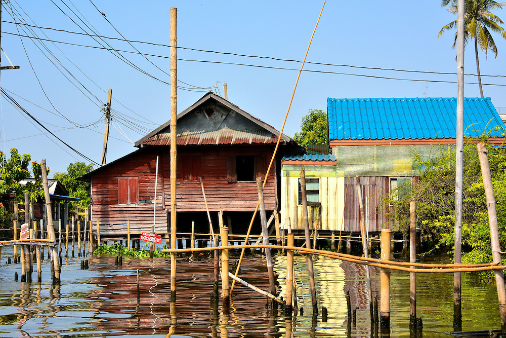 Homes Along Canals in Bangkok, Thailand <br /> Numerous Thai people live along the canals of Bangkok in elevated homes.  Some are decrepit huts and some are mansions but most are similar to these.  The bamboo stalks are used to moor their boats.