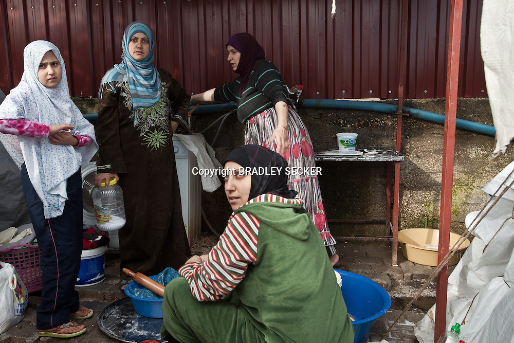 Syrian women wash dishes and prepare food in the sink shared by 35 families in Yayladagi refugee camp for Syrians in southern Turkey. 12/21/2012 Bradley Secker for the Washington Post