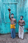 Two young men with candle offering and ringing bell  in front of green wall,  Mawlamyine