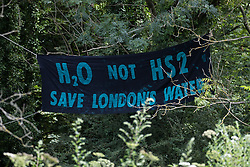Denham, UK. 13 July, 2020. A banner reading 'H20 Not HS2' hangs close to Denham Protection Camp alongside the river Colne. Environmental activists from HS2 Rebellion are seeking to hinder or prevent the construction of the £106bn HS2 high-speed rail link, which will remain a net contributor to CO2 emissions during its projected 120-year lifetime.