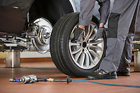 Low section of male mechanic repairing car's tire in repair shop