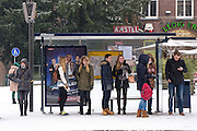 Mensen wachten in Utrecht in de kou bij een bushalte aan het Ledig Erf. De sneeuwval in het westen van land heeft de nodige overlast veroorzaakt.
