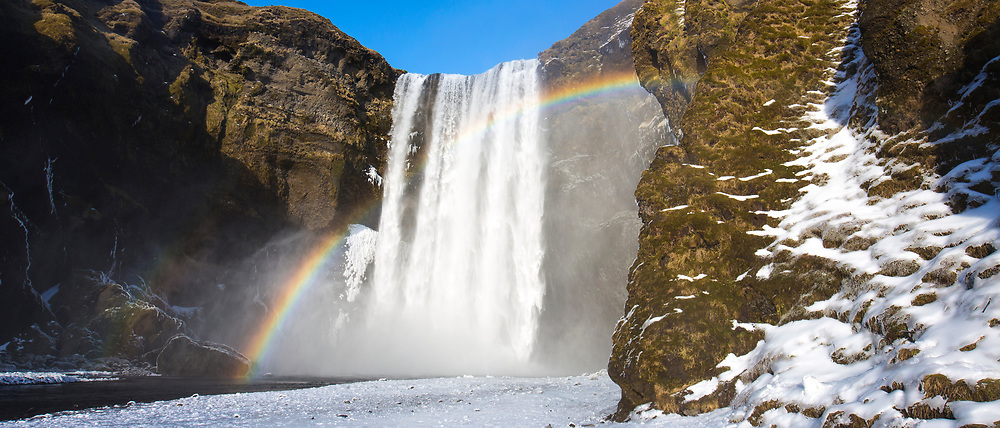 Rainbow at spectacular Skogar waterfall - Skogarfoss - in South Iceland with gushing glacial melting waters