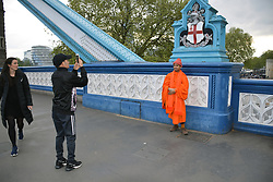 Buddhist monk having his picture taken on Tower Bridge, London UK April 2019