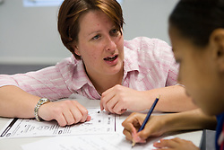 Technology Teacher giving individual tuition to secondary school student on products with mechanisms,