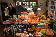 "(MODEL RELEASED IMAGE). The Melander family: Jörg, 45, and Susanne, 43, with sons Kjell, 10, and Finn, 14 in the dining room of their home in Bargteheide, Germany, with a week's worth of food. Cooking methods: electric stove, microwave, and outdoor BBQ grill. Food preservation: refrigerator-freezer, freezer chest. Favorite foods? Jörg: fried potatoes with onions, bacon, and herring. Finn: fried noodles with eggs, cheese. Kjell: pizza, vanilla pudding. Susanne: ""anything that's fresh and good."" /// The Melander family is one of the thirty families featured in the book Hungry Planet: What the World Eats (p. 132). Food expenditure for one week: $500.07 USD. (Please refer to Hungry Planet book p. 133 for the family's detailed food list.)"