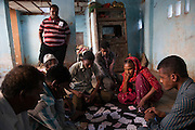 Local Sidi members play cards during the heat of the day in a small community in central Ahmedabad exclusively occupied by Sidi families. It surrounds a Bava Gor shrine, the sidi patron saint for Muslim Sidi's, and the local side's are tasked with looking after the shrine
