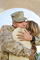 Soldier embracing wife outdoors
