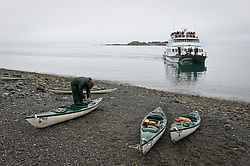 The daily tour boat, Baranof Wind, picks up an unidentified kayaker on the beach at Sebree Island in Glacier Bay National Park and Preserve in southeast Alaska. The Baranof Wind drops off and picks up wilderness kayakers at several set locations in the park.