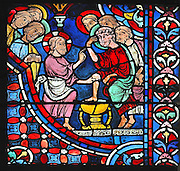 Jesus, a towel tied around his waist, acts as a servant and washes the feet of Peter in a chalice-like basin. He teaches the apostles to wash each others feet in a gesture of equality and humility. Section of the washing of the feet, from the Apostles window, 1212-25, in the axial chapel in the ambulatory of Chartres Cathedral, Eure-et-Loir, France. This window represents the birth of the Church, as the apostles are the first pillar of the church and therefore has the site with the most sunlight to illuminate the colours. Chartres cathedral was built 1194-1250 and is a fine example of Gothic architecture. Most of its windows date from 1205-40 although a few earlier 12th century examples are also intact. It was declared a UNESCO World Heritage Site in 1979. Picture by Manuel Cohen